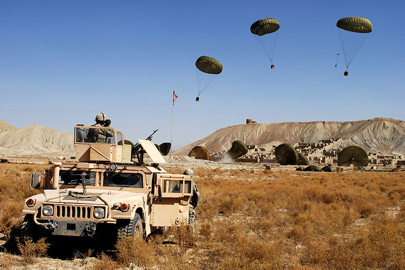 us army armored vehicle with air drops in background